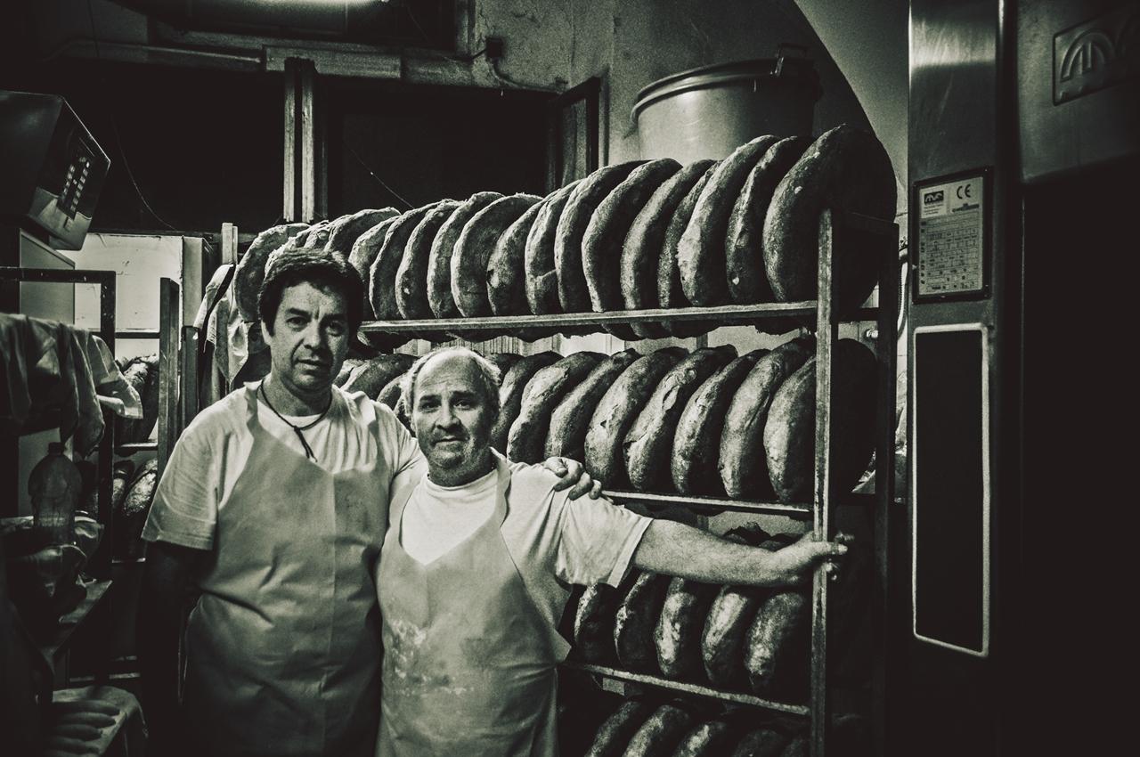 Dopo una notte di lavoro, le pagnotte sono pronte per raffreddarsi ed essere vendute al banco del forno. Alle spalle di Antonio (a sinistra) e Rocco (a destra) il risultato di una notte di lavoro.
